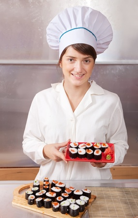 Cook woman with cooked  sushi rolls in kitchen photo