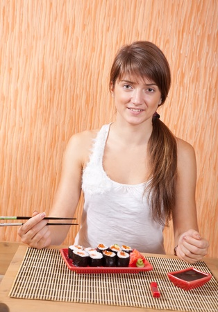 Young woman eating sushi rolls photo
