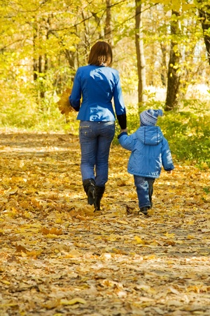 Happy woman with son walking in autumn park photo