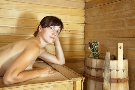 naked girl lying on  bench in  sauna photo