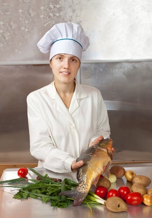 Cook woman  cooking fish  in kitchen photo