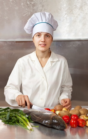 Cook woman with carp fish in kitchen Stock Photo - 11069960