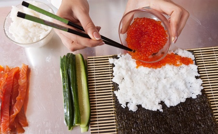 Closeup of cook making  Japanese sushi rolls  with caviar photo
