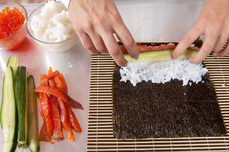 Close up of woman making  Japanese sushi rolls photo