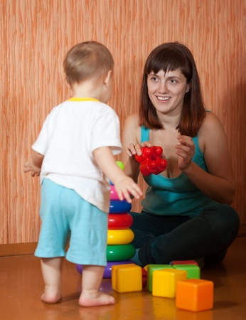 woman only: Happy mother and baby plays with toy blocks in home. Focus on woman only