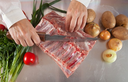 koken handen snijden van rauw vlees op keukentafel Stockfoto
