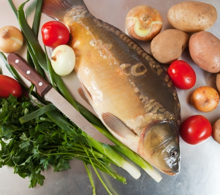 Raw fresh carp fish with vegetables photo