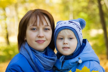 Happy mother with little boy outdoor in autumn photo