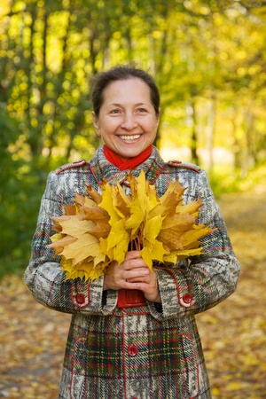 Portrait of mature woman against autumn landscape photo