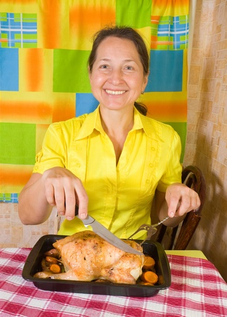Mature woman with cooked stuffed chicken on roasting pan in kitchen Stock Photo - 11069813