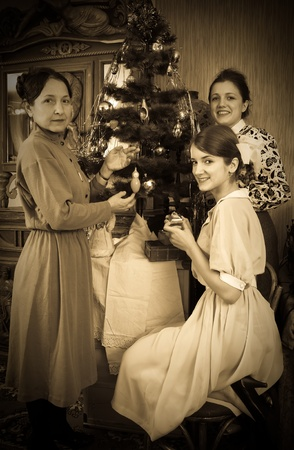 Vintage photo of  daughters with mother decorating Christmas tree at home photo