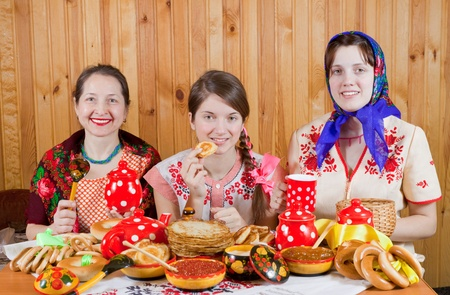 Women in traditional  clothes eating pancake with tea during  Shrovetide Stock Photo - 11069810