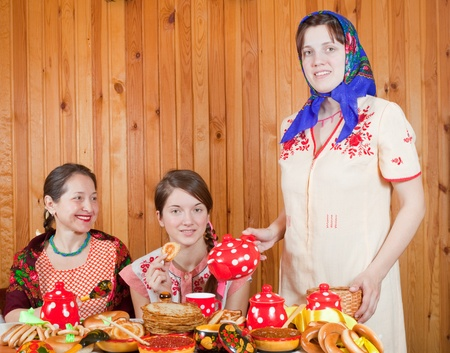 Women in traditional  clothes eating pancake with tea during  Shrovetide photo