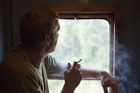Man smoking in vestibule train carriage photo