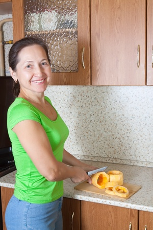 farcie:  cook hands cutting vegetable marrow  on cutting board. See in series stages of cooking of stuffed vegetable marrow