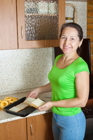 Woman puts toast bread into roasting tray.
