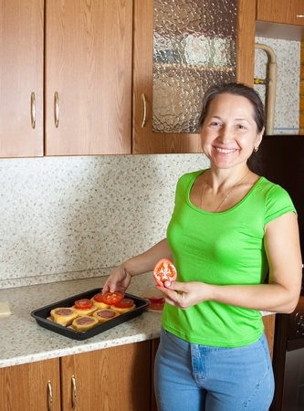 farci: Woman adds tomato on stuffed vegetable marrow. See in series stages of cooking of stuffed vegetable marrow