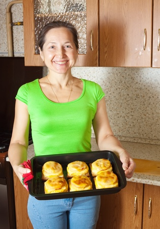 Woman with cooked baked stuffed vegetable marrow.