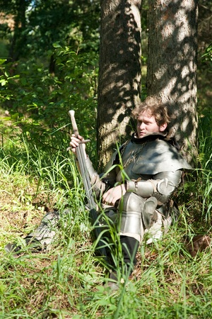 Knight sitting under the tree at forest photo