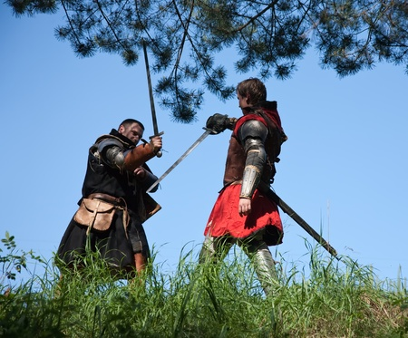 duelling: Two knights in armor is fighting  against blue sky