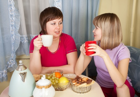 two   girls sitting in kitchen, gossiping and drinking tea photo
