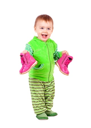 Happy toddler holds shoes. Isolated over white background photo