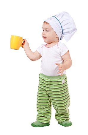 Baby cook in toque with cup over white background photo