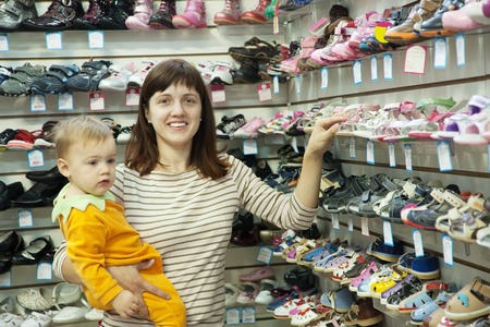 Happy mother with child chooses baby shoes at fashionable shop
