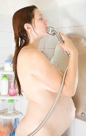 8 months pregnant woman in bath with shower Stock Photo - 11191396
