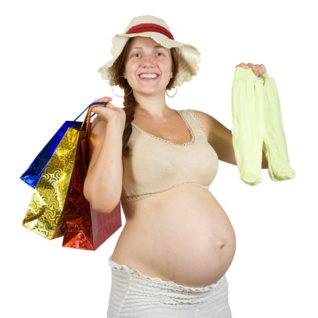 pregnant woman with shopping bags and babies clothes over white photo