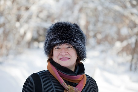 Outdoor winter portrait of mature woman in wintry forest photo