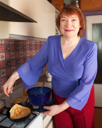 Mature woman cooking pancakes at her kitchen photo