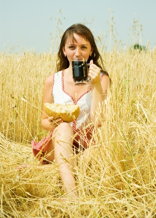 Girl  with beer and bread  at wheat field photo