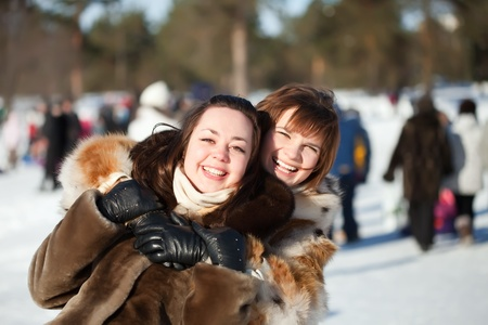 Two happy girls plays in winter park photo