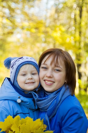 Happy woman with her son in autumn park photo