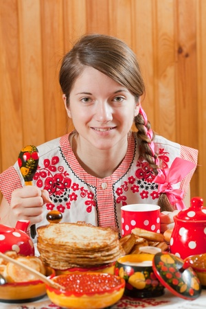 Girl in traditional  clothes eating pancake with caviare during  Shrovetide photo