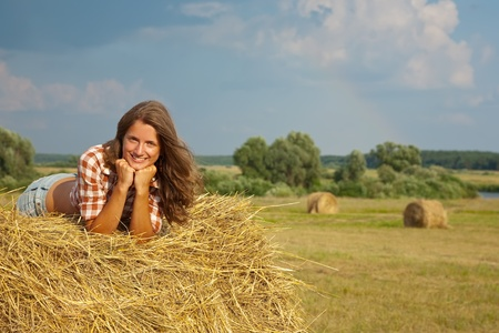 Pretty girl resting on straw bale photo