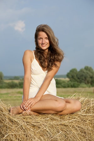 Beautiful girl enjoying the nature on a  hay photo