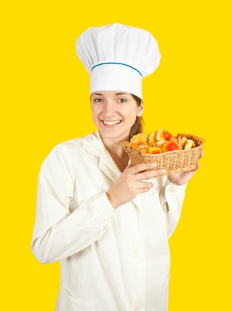 cooky: Portrait of female cook with sweets over yellow background