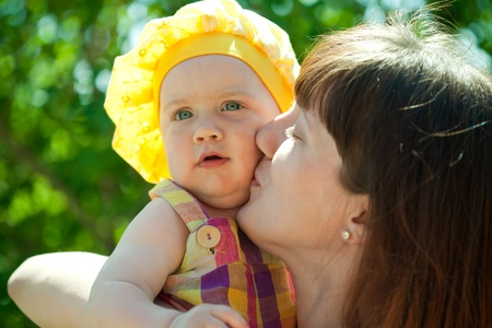 Happy mother kissing  baby daughter  against nature photo