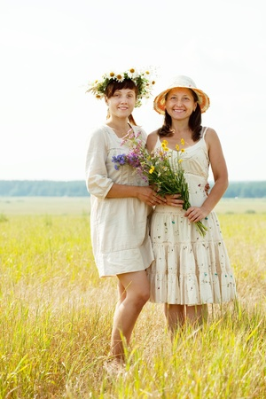 Portrait of two happy women with flowers in summer field photo