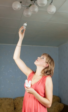 Girl changes light bulb at her home photo