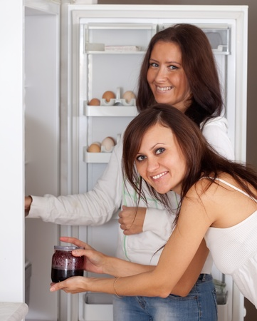 Two women looking for something in the  refrigerator at home photo
