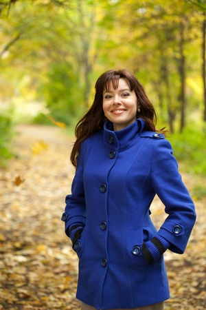 Girl in blue coat at autumn park  Stock Photo - 11480005