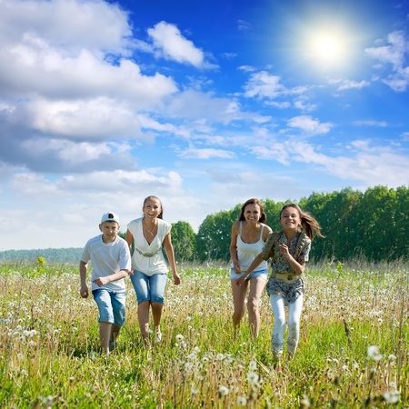Happy mothers with teenagers running in meadow  photo