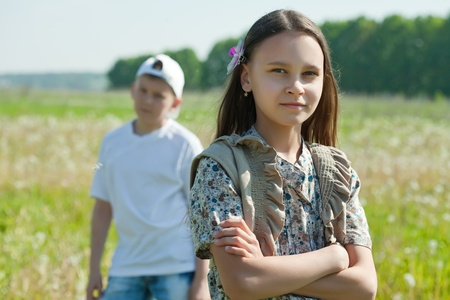 brother sister fight: quarrel in the park. Sad girl and boy Stock Photo
