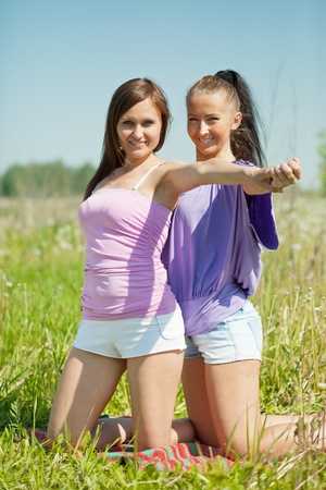 Two smiling pretty girlfriends sitting in field Stock Photo - 11480040