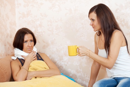 Woman gives cup to unwell friend in home Stock Photo - 11480030