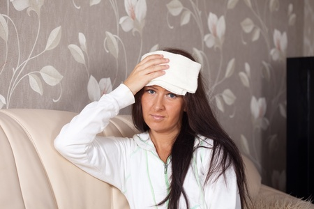 Suffering woman stupes  towel to her head Stock Photo - 11480004