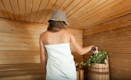 girl is steamed in the sauna with birch twigs photo